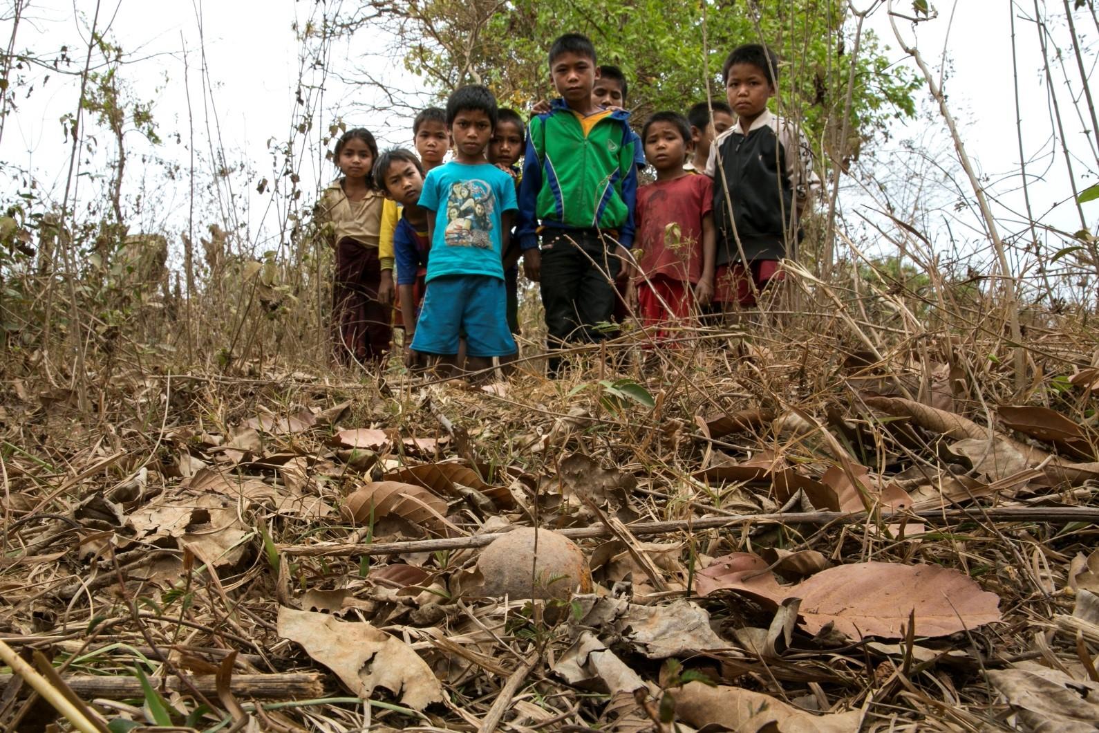 District de Toumlan, village de Nadoo Yai. Des enfants regardent une sous-munition non explosée qui a été trouvée près de leur village.