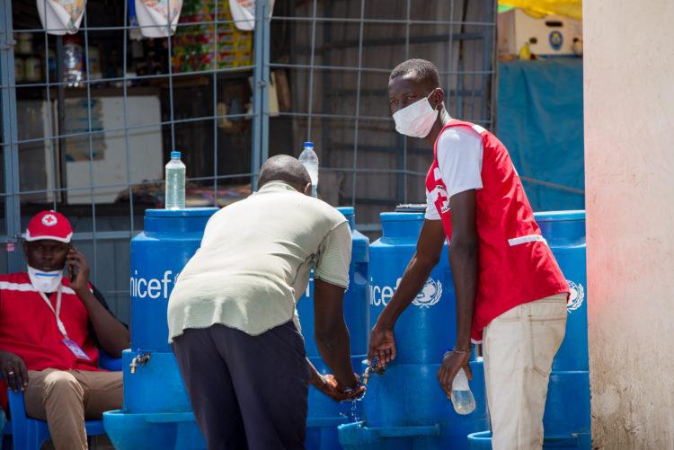 Les volontaires de la Croix-Rouge sénégalaise portant un masque font de la sensibilisation au lavage de mains.